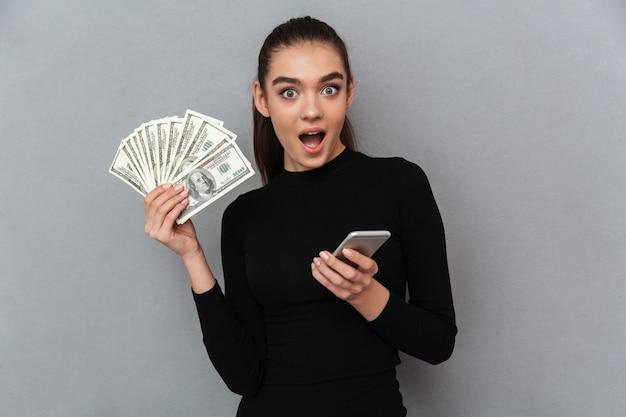 Verraste gelukkige donkerbruine vrouw die in zwarte kleren geld houdt
