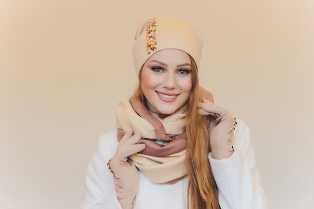 Verraste gelukkige mooie vrouw die zijdelings in opwinding kijkt. kerstmismeisje die gebreide warme die hoed en vuisthandschoenen dragen, op grijze achtergrond worden geïsoleerd.