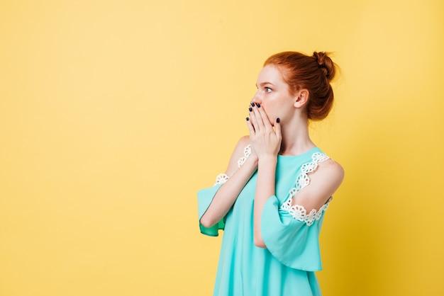 Verraste gembervrouw die in kleding weg en mond behandelt kijkt