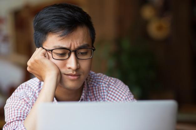 Verraste jonge aziatische mannelijke student zittend op laptop