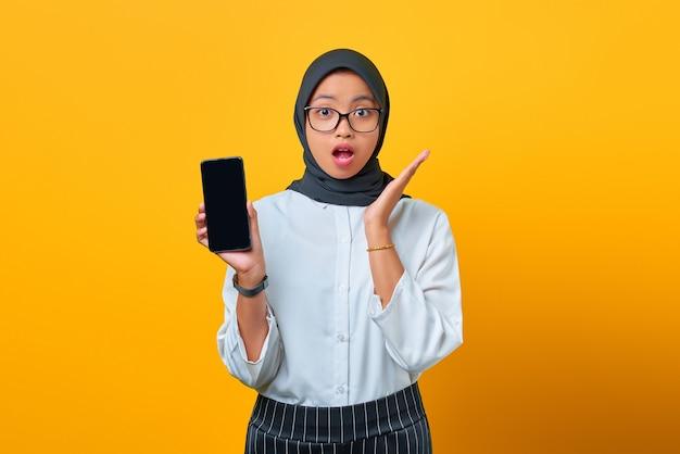 Verraste jonge aziatische vrouw die het lege scherm van de mobiele telefoon toont dat over gele achtergrond wordt geïsoleerd