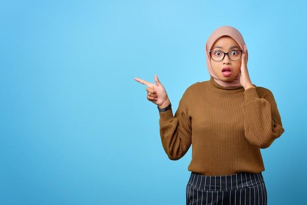 Verraste jonge aziatische vrouw die met de vingers wijst naar kopieerruimte op blauwe achtergrond