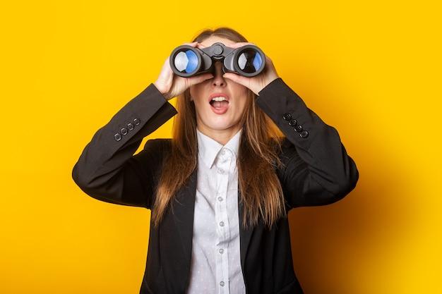 Verraste jonge bedrijfsvrouw die door een verrekijker op geel kijkt.