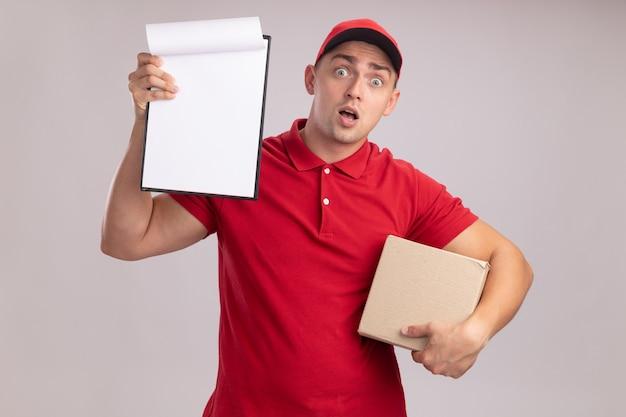 Verraste jonge bezorger die uniform met de doos van de glbholding draagt en klembord opheft dat op witte muur wordt geïsoleerd
