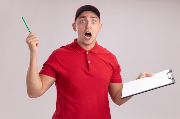 Verraste jonge bezorger die uniform met het klembord en het potlood van de glbholding op witte muur wordt geïsoleerd
