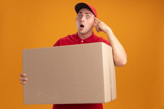 Verraste jonge bezorger die uniform met pet draagt die grote doos houdt die vinger op tempel zet die op oranje muur wordt geïsoleerd