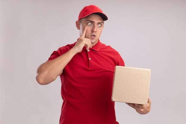 Verraste jonge bezorger die uniform met pet draagt en doos bekijkt die vinger op tempel zet die op witte muur wordt geïsoleerd