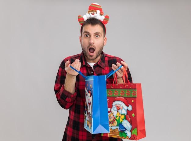 Verraste jonge blanke man met kersthoofdband met kerstcadeautassen die er een openen die geïsoleerd op een witte muur met kopieerruimte kijkt