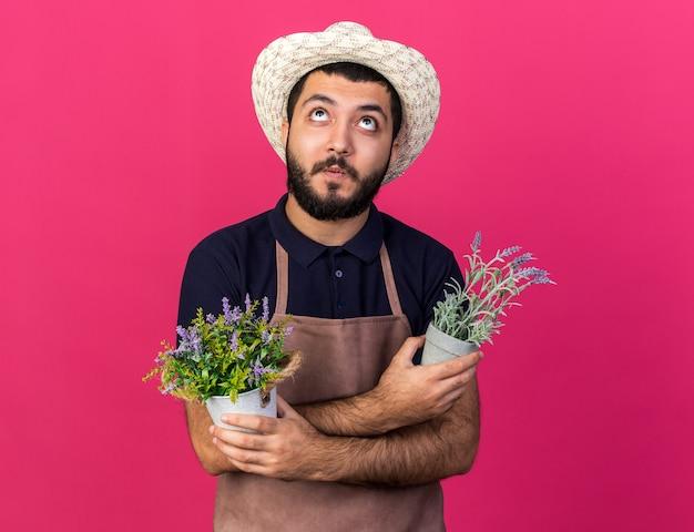 Verraste jonge blanke mannelijke tuinman met een tuinhoed die bloempotten vasthoudt en armen kruist en omhoog kijkt geïsoleerd op roze muur met kopieerruimte