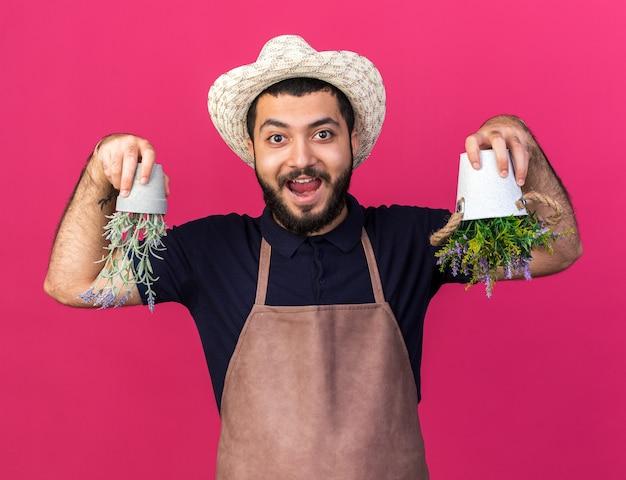 Verraste jonge blanke mannelijke tuinman met een tuinhoed met bloempotten ondersteboven geïsoleerd op een roze muur met kopieerruimte