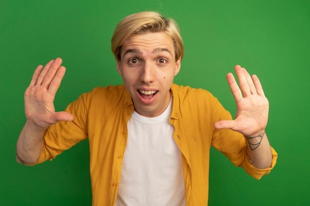 Verraste jonge blonde kerel die gele t-shirt draagt die stopgebaar toont dat op groen wordt geïsoleerd