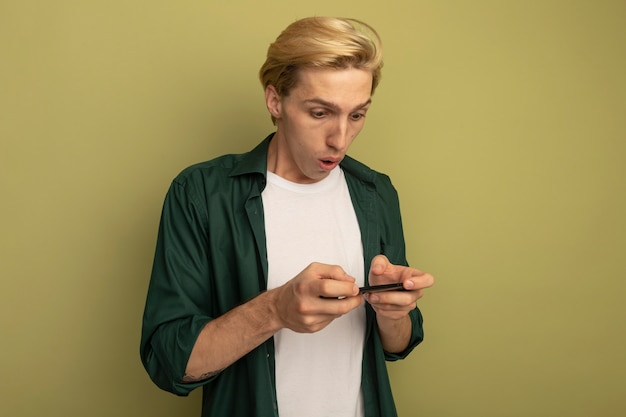 Verraste jonge blonde kerel die groen t-shirt draagt dat op telefoon speelt