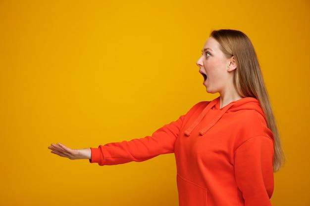 Verraste jonge blonde vrouw die zich in profielmening uitstrekt uit hand die kant bekijkt
