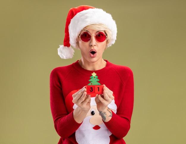 Verraste jonge blonde vrouw met kerstmuts en kersttrui van de kerstman met bril met kerstboomspeelgoed met datum die geïsoleerd op olijfgroene muur met kopieerruimte kijkt