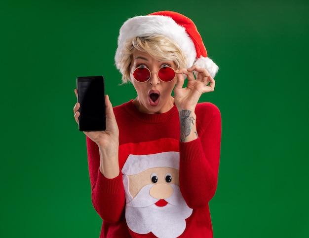 Verraste jonge blonde vrouw met kerstmuts en kersttrui van de kerstman met een bril op zoek naar een grijpbril met mobiele telefoon geïsoleerd op een groene muur met kopieerruimte