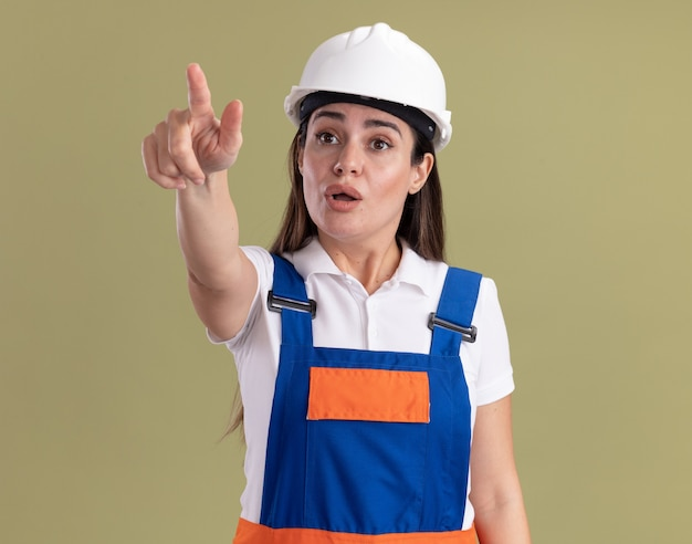 Verraste jonge bouwersvrouw in eenvormige punten aan kant die op olijfgroene muur wordt geïsoleerd