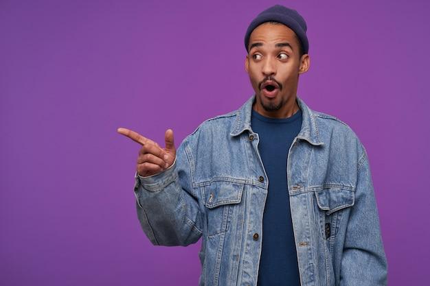 Verraste jonge bruinogige, donkere bebaarde man, gekleed in vrijetijdskleding, toont zich verbaasd opzij met wijsvinger en houdt de mond open, staande over de paarse muur