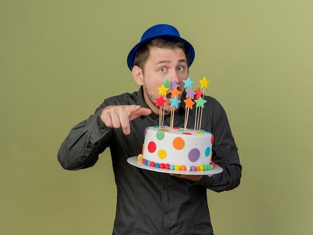 Verraste jonge feestmens die een zwart overhemd en een blauwe hoed draagt die cake houdt en je gebaar toont dat op olijfgroen wordt geïsoleerd Gratis Foto