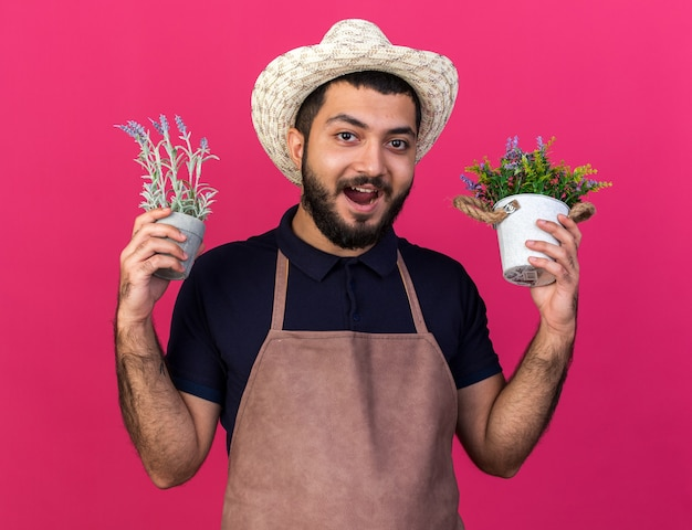 Verraste jonge kaukasische mannelijke tuinman die een tuinhoed draagt die bloempotten houdt die op roze muur met exemplaarruimte worden geïsoleerd