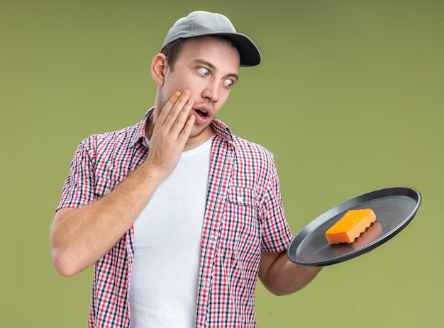 Verraste jonge kerel die een dop draagt en naar een spons kijkt die op een dienblad de hand op de wang legt die op een olijfgroene muur is geïsoleerd?