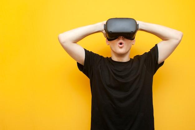 Verraste jonge kerel met vr-bril op een gele achtergrond kijkt naar de horror en het geschreeuw, man gebruikt een virtual reality-bril en wees bang