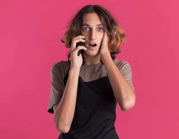 Verraste jonge knappe kapper in uniform pratend aan de telefoon en hand op het gezicht geïsoleerd op een roze muur met kopieerruimte?