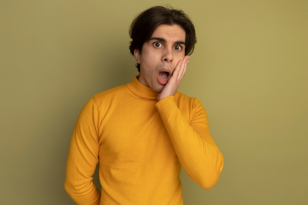 Verraste jonge knappe kerel die gele coltrui draagt ?? die hand op wang zet die op olijfgroene muur wordt geïsoleerd