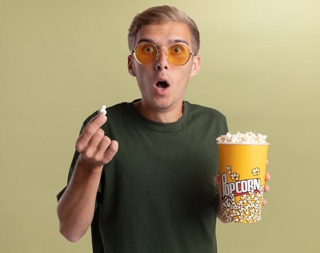 Verraste jonge knappe kerel die groen overhemd met glazen draagt die emmer popcorn met popcornvrede houdt die op olijfgroene muur wordt geïsoleerd