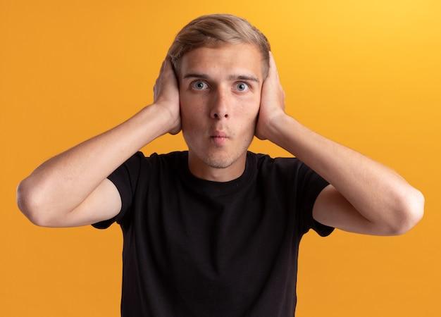 Verraste jonge knappe kerel die zwart overhemd draagt dat handen op oren zet die op gele muur worden geïsoleerd