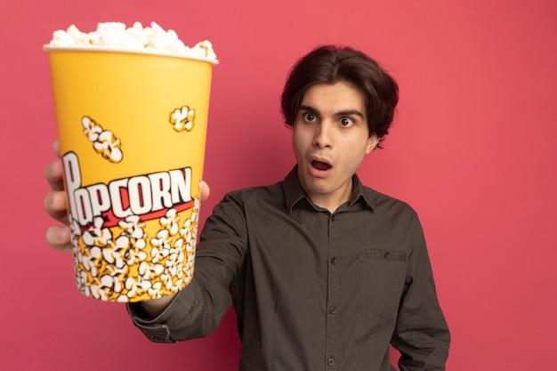 Verraste jonge knappe kerel die zwart t-shirt draagt dat emmer popcorn aan voorzijde vasthoudt die op roze muur wordt geïsoleerd