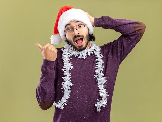 Verraste jonge knappe kerel met kerstmuts met slinger op nekpunten aan de zijkant die hand op het hoofd zetten geïsoleerd op olijfgroene muur met kopieerruimte