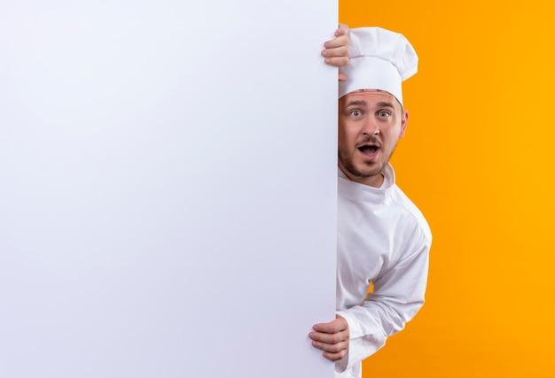 Verraste jonge knappe kok in eenvormige chef-kok die zich achter witte muur bevindt en het geïsoleerd op oranje ruimte houdt