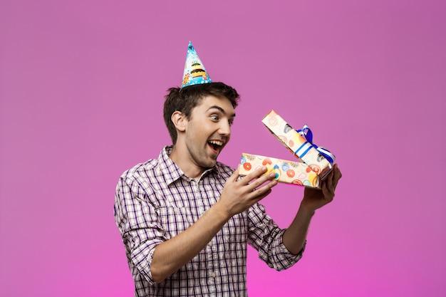Verraste jonge knappe mens die verjaardagsgift over purpere muur openen.