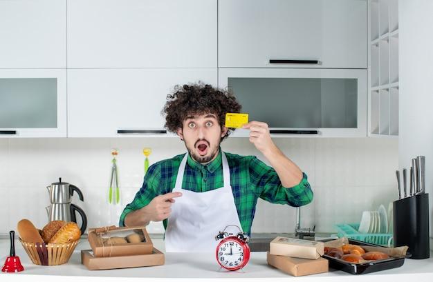 Verraste jonge man die achter de tafel staat met verschillende gebakjes erop en een bankkaart in de witte keuken laat zien