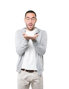 Verraste jonge man die iets met zijn hand houdt