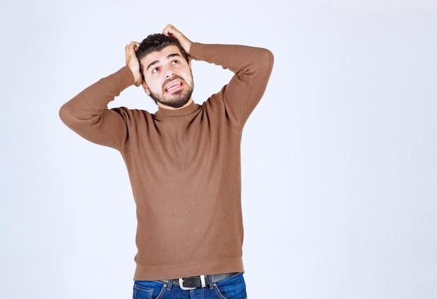 Verraste jonge man met zwart haar die zijn handen op het hoofd houdt.