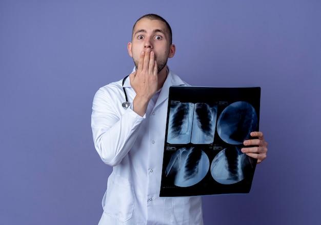 Verraste jonge mannelijke arts die een medische mantel en een stethoscoop om zijn nek draagt die röntgenfoto houdt en de hand op de mond legt die op paarse muur wordt geïsoleerd