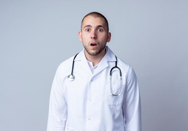 Verraste jonge mannelijke arts die medische mantel en stethoscoop om zijn hals draagt die voorzijde bekijkt die op witte muur wordt geïsoleerd