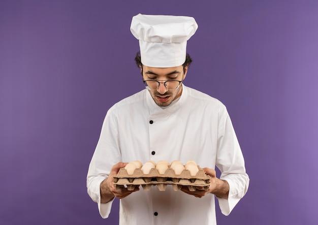 Verraste jonge mannelijke kok die eenvormige chef-kok en glazen draagt die partij eieren op paars houdt