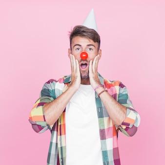 Verraste jonge mens met rode clownneus die zich tegen roze achtergrond bevinden