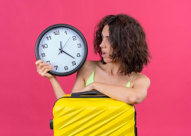 Verraste jonge mooie reizigersvrouw met koffer en klok en klok op geïsoleerde roze muur bekijken