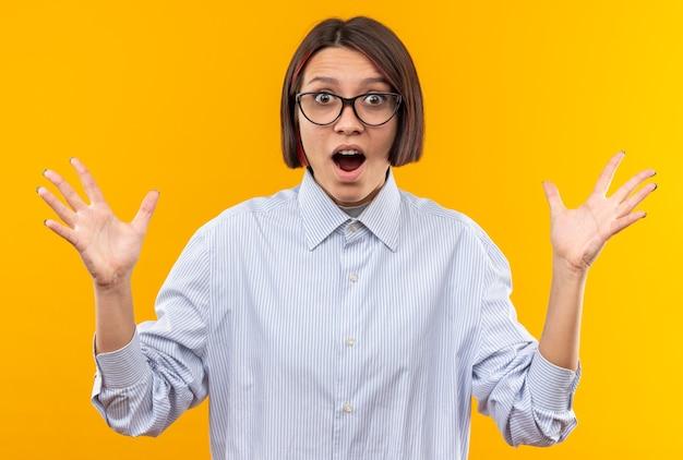 Verraste jonge mooie vrouw die een bril draagt die handen uitspreidt die op oranje muur worden geïsoleerd