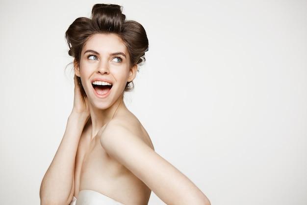Verraste jonge mooie vrouw die in haarkrulspelden met geopende mond glimlacht. schoonheid en spa concept.