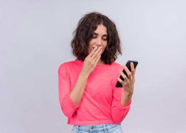 Verraste jonge mooie vrouw die mobiele telefoon houdt en hand op mond op geïsoleerde witte muur met exemplaarruimte zet