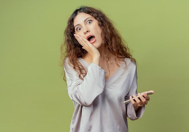 Verraste jonge mooie vrouwelijke kantoormedewerker die telefoon houdt en hand op wang zet die op olijfgroene muur wordt geïsoleerd