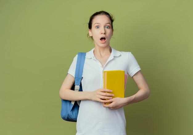 Verraste jonge mooie vrouwelijke student die het boek van de achterzakholding draagt ?? die camera bekijkt die op groene achtergrond met exemplaarruimte wordt geïsoleerd