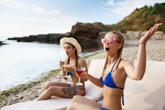 Verraste jonge mooie vrouwen die op chaises dichtbij overzees liggen
