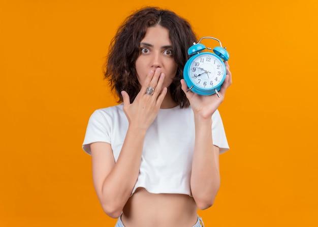 Verraste jonge mooie wekker van de vrouwenholding en hand op mond zetten op geïsoleerde oranje muur met exemplaarruimte