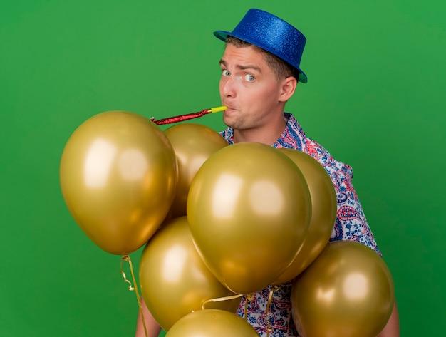 Verraste jonge partij kerel die blauwe hoed draagt ?? blazende partijventilator die zich achter ballons bevindt die op groen worden geïsoleerd