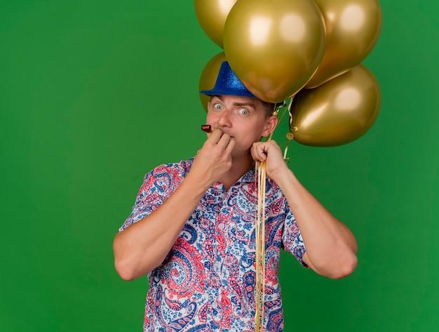 Verraste jonge partij kerel die blauwe hoed draagt die ballons houdt die partijventilator blazen die op groen wordt geïsoleerd